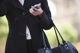 Businesswoman with handbag and mobile  mid section