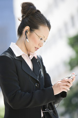 Young businesswoman using mobile outdoors