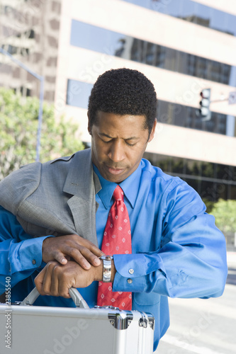 Mid-adult businessman checking time