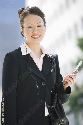 Young businesswoman using mobile outdoors  portrait