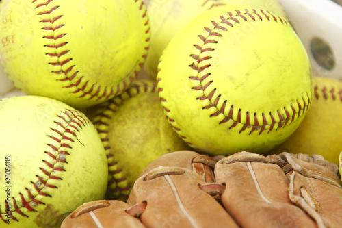 Pile of softballs and baseball glove - 23856115
