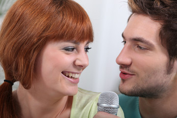 Portrait of a smiling couple singing in a microphone