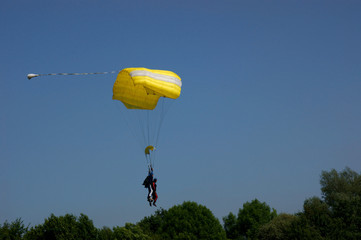 A yellow tandem skydive parachute against a blue sky