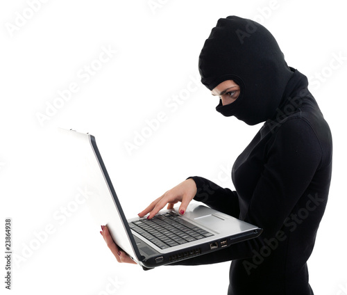 criminal woman in balaclava with the laptop