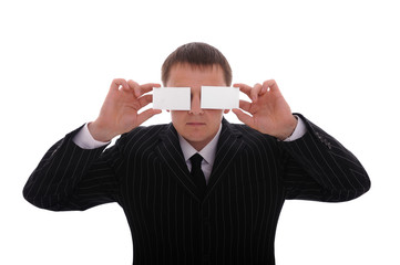 Businessman covering his eyes with business cards