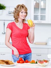 Woman drinking juice and cooking