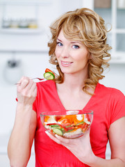 Woman eating heathy salad in the kitchen