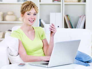 Woman with cup of tea using laptop