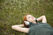 Young  fashion with headphones lying at green grass.
