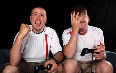 Two football supporters playing soccer on games console