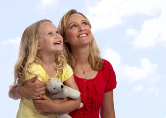 Happy blond mother and daughter looking up into the sky