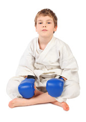 little boxer boy in white dress and blue boxing gloves sitting