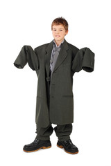 little boy in big grey man's suit and boots standing isolated