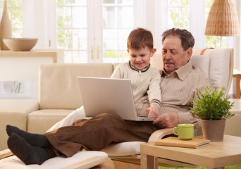 Grandfather and grandson using computer together