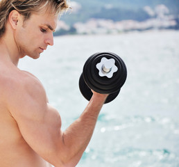 Muscular man lifting weight on the beach
