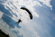 Silhouette of the landing parachutist against the evening sky