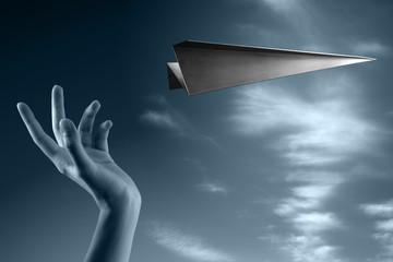 mano che lancia un aereo in acciaio