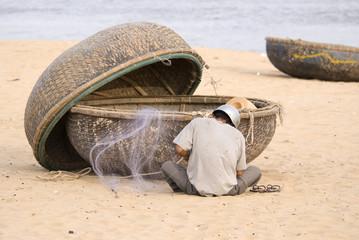 Fisherman who is repairing his fishing net