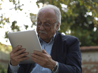 old man using tablet computer e-book reader
