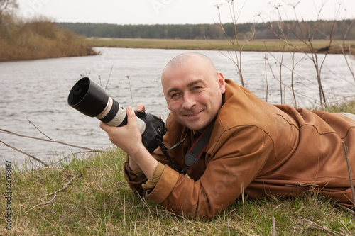men with photocamera near river