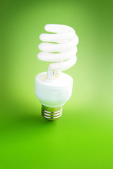 Fluorescent light bulb standing on green background
