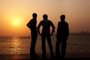 3 Indian guys watch the sunset over Mumbai