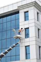 Window cleaner washing the office block's windows.