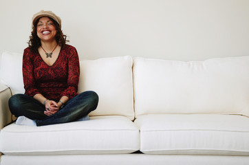 Laughing Woman Sits On Sofa