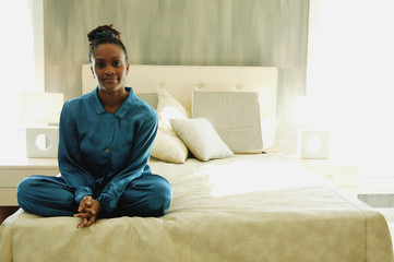Woman Sits Cross-Legged On A Bed