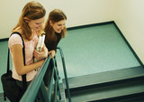 Students Looking Over Handrail In Stairway poster
