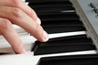Closeup of a male hand playing a piano