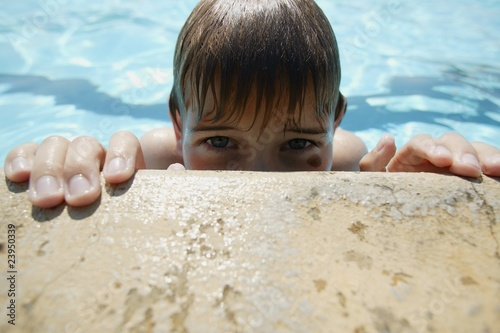 Boy Creeps Up On Side Of Pool