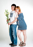 Young beautiful couple expecting a baby with white lilies