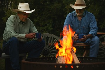 Two Men Sitting By A Fire