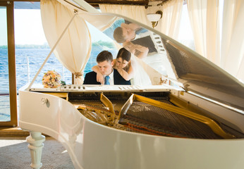 Bride and groom at the white grand piano