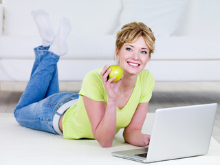 Woman with laptop eating apple