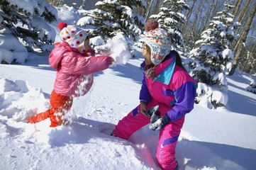 Mother And Daughter Having A Snowball Fight