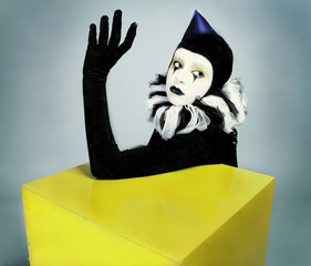 Сircus fashion mime posing near a yellow square