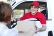 postal delivery courier in a van delivering package