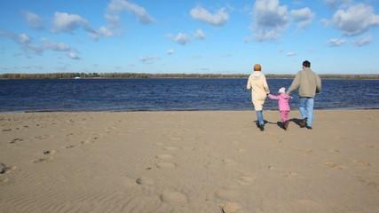 family runs on sandy beach