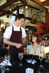 waiter talking to costumer at the restaurant