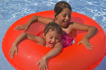 Two Girls With Rubber Ring In Pool