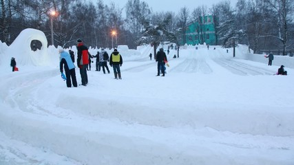 Winter day: many people slide from ice slides