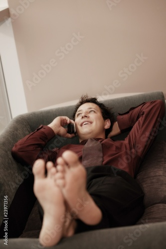 Man Talking On Cell Phone While Relaxing On Couch