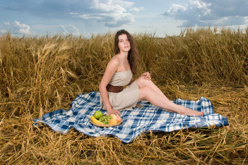 Beautiful slavonic girl on picnic in wheat field
