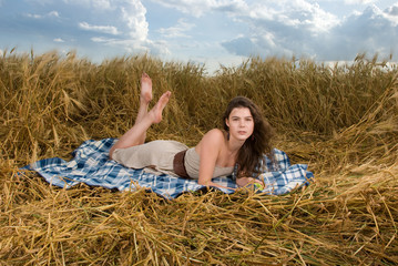 Beautiful slavonic girl on picnic in wheat field with apple