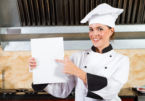chef holding a white board or menu in kitchen
