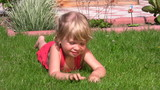 little girl lying in outlet and picks grass