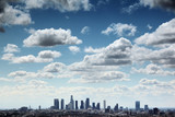 Downtown Los Angeles skyline under blue sky with scenic clouds poster
