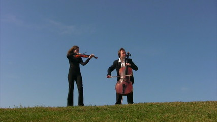 man and woman plays violoncellos on hill
